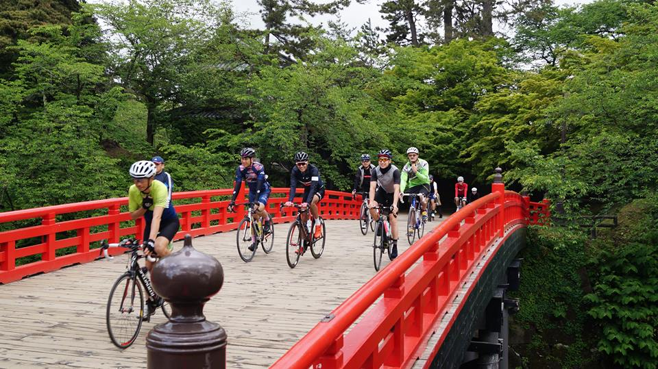 outlands bike tour cyclists ride over red bridge hirosaki park